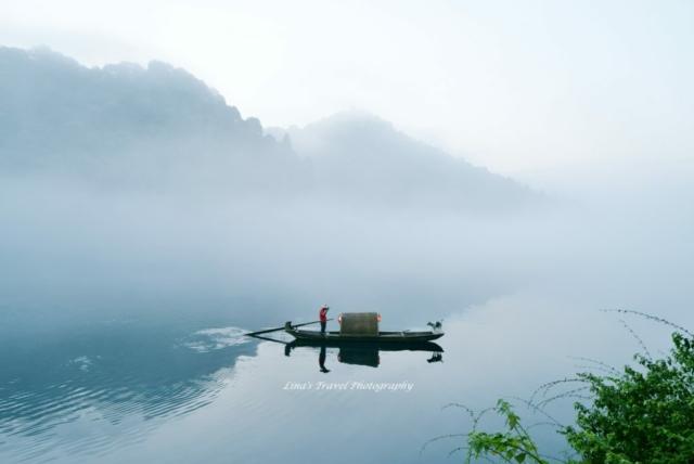 Fisherman and his friend on misty Little East Lake, Dongjiang County, Zixing, Chenzhou, Hunan, China