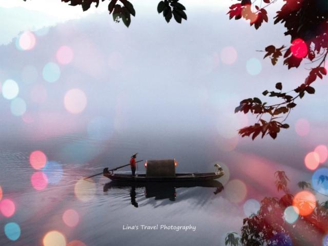 Dreamlike fishing by a single fisherman with his dog a misty morning at East Lake, Dongjiang County, Zixing, Chenzhou, Hunan, China