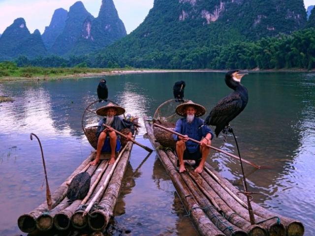 Cormorant fisherman waiting for sunset at Li River, Yangshuo, Guangxi, China