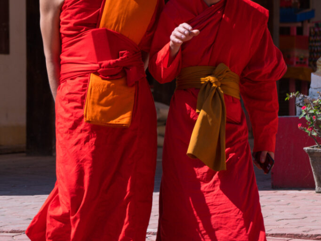 Colourful monks in sunshine, Wat That, Vang Vieng, Laos